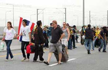 Police facilitate foreigners to go through blockage of anti-government protesters at Suvarnabhumi Airport on Tuesday after they were unable to reach the departure louge.