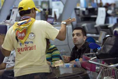 A stranded Western tourist listens to an explanation of issues by a supporter of the People's Alliance for Democracy (PAD) Wednesday, Nov. 26, 2008, at Suvarnabhumi airport in Bangkok, Thailand. Thailand. Thousands of tourist were stranded Tuesday night when members of the PAD swarmed the airport causing it to shutdown. The protesters are demanding the resignation of Prime Minister Somchai Wongsawat. (AP Photo/David Longstreath)