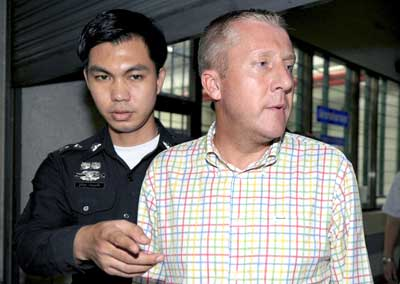 Britain Michael Bryan Smith (R), accused of embezzlement in Dubai, is escorted by Thai policeman at the criminal court in Bangkok on May 21, 2009. Thai police arrested Smith in Bangkok's red light district after he spent eight months on the run for allegedly embezzling 150 million USD from a company in Dubai