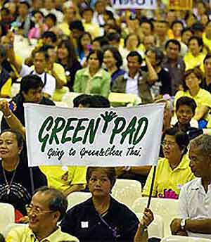 A member of the People's Alliance for Democracy displays a ''green'' banner during an assembly at Rangsit University yesterday, after the PAD changed its theme colour from yellow to yellow and green.